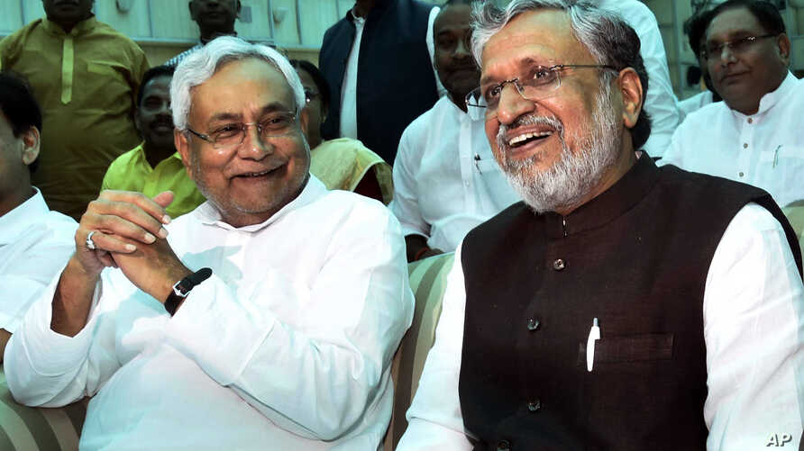 Bihar Chief Minister Nitish Kumar, left, and Deputy Chief Minister Sushil Kumar Modi share a light moment after oath taking ceremony at Raj Bhawan in Patna, India, July 27, 2017.