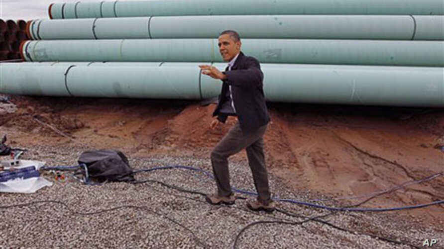 President Barack Obama waves as he arrives at the TransCanada Stillwater Pipe Yard in Cushing, Oklahoma, March, 22, 2012.