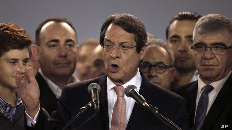 Cyprus President Nicos Anastasiades, center, speaks to supporters who gathered at a stadium to attend his inauguration ceremony in Nicosia, Sunday, Feb. 4, 2018.