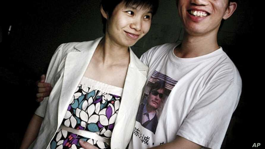 In this July 6, 2007 file photo, Hu Jia, right, and Zeng Jinyan, husband-and-wife activists, pose for a picture at their home in Beijing. Zeng said she visited Hu, who was jailed for sedition more than three years ago, in prison June 20, 2011. Jia wa