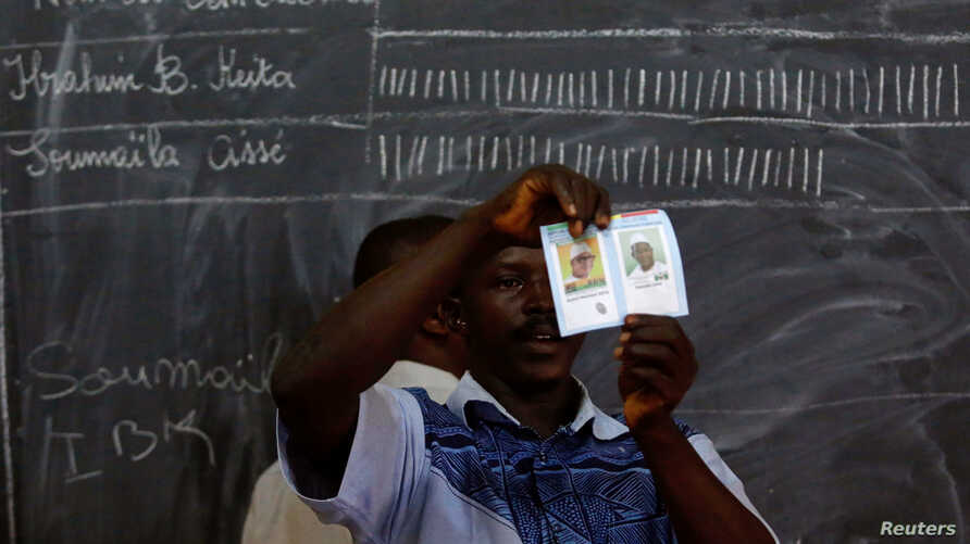 Election workers count ballots during a runoff presidential election in Bamako, Mali, Aug. 12, 2018.
