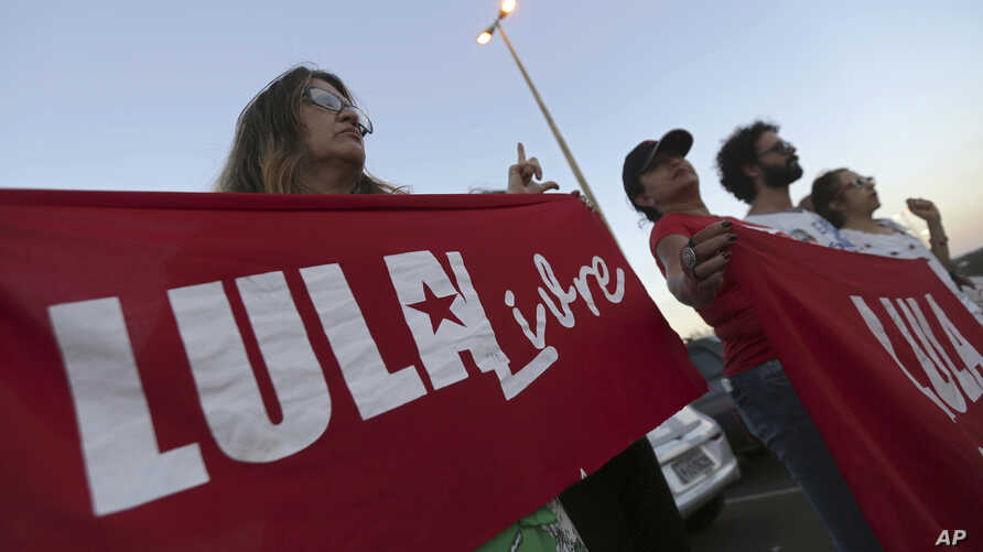 "Supporters of Brazil's former President Luiz Inacio Lula da Silva, display banners saying ""Free Lula"" in Portuguese during a protest in front of the Superior Electoral Court, Brasilia, Aug. 31, 2018."