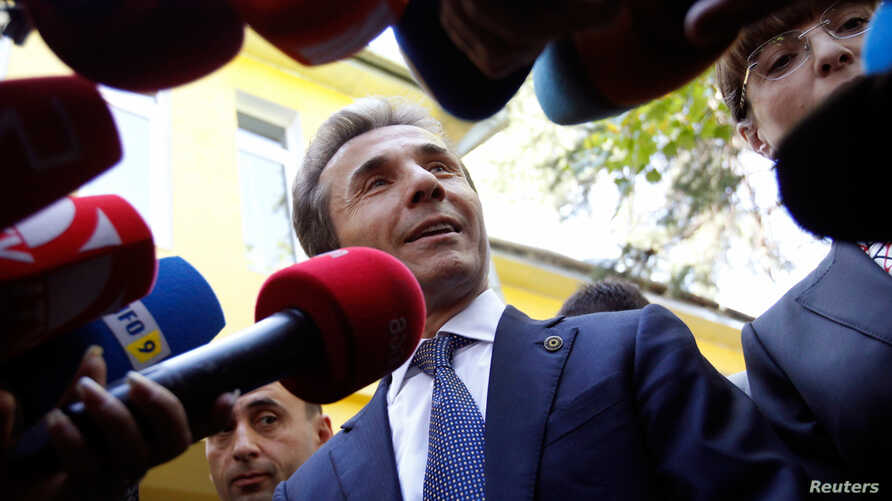 Leader of the opposition Georgian Dream coalition Bidzina Ivanishvili (C) addresses the media near his wife Eka Khvedelidze (R), who voted at a polling station during the parliamentary election, in Tbilisi October 1, 2012.