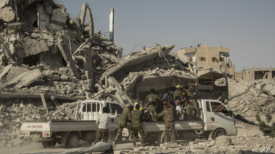 """FILE - Members of the U.S.-backed Syrian Democratic Forces (SDF) ride near near the main traffic circle in Raqqa, Syria, Oct. 20, 2017. The day before, the SDF declared from the stadium during a ceremony the """"total liberation"""" of Raqqa, the capital o"""