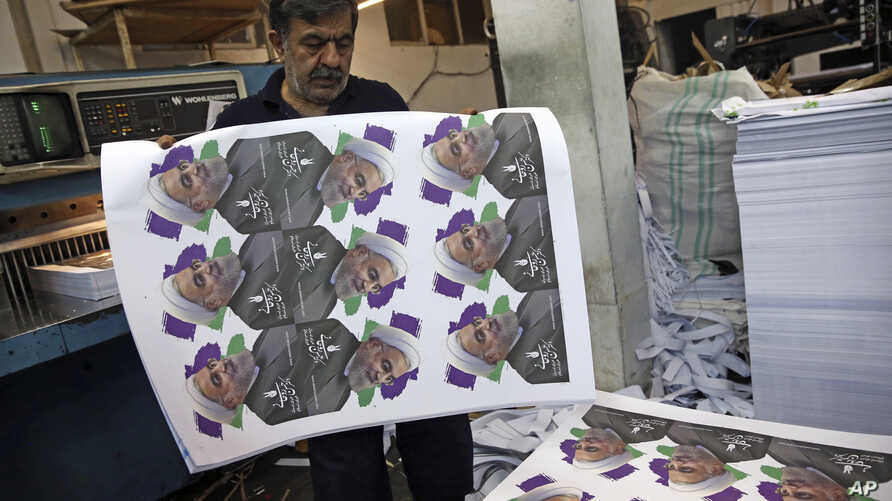 Kianoush Mahmoudzadeh prepares electoral posters of President Hassan Rouhani for the May 19 presidential election campaign in a printing house in Tehran, Iran, May 10, 2017.