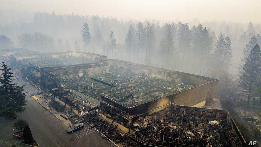 Smoke hangs over the scorched remains of Old Town Plaza following the wildfire in Paradise, Calif., Nov. 15, 2018. The shopping center housed a grocery store and other businesses.