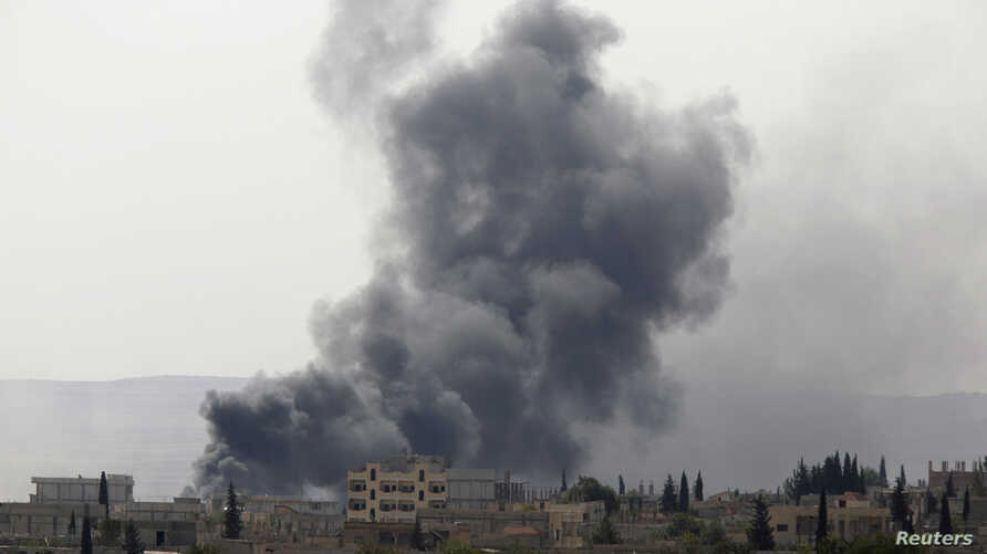 Smoke rises from the Syrian town of Kobani, seen from near the Mursitpinar border crossing on the Turkish-Syrian border in the southeastern town of Suruc, Sanliurfa province, Oct. 3, 2014.