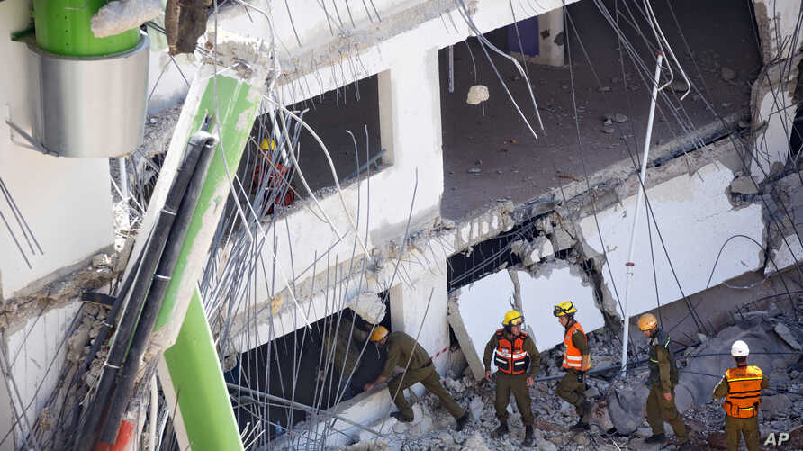 Israeli soldiers from the Home Front Command unit inspect the site of a collapsed multilevel underground parking in Tel Aviv, Sept. 5, 2016.