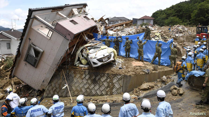 Rescue workers look for missing people in a house damaged by heavy rain in Kumano town, Hiroshima Prefecture, Japan, July 9, 2018. (Kyodo/via Reuters)