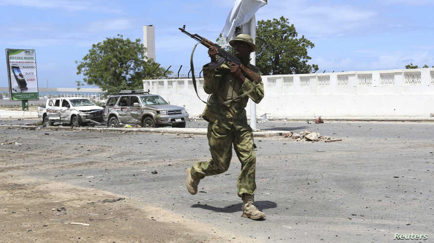 Somali government soldier runs to take position in front of the Parliament during fighting between them and Al shabaab militia in the capital Mogadishu, May 24, 2014.