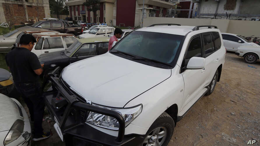 Pakistani journalists examine a car of American diplomate parked inside a police station after an accident in Islamabad, April 7, 2018.