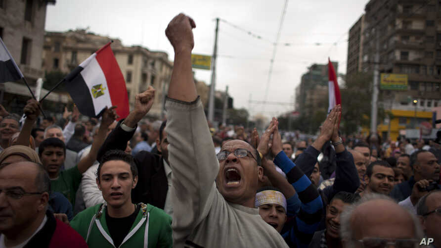 Egyptian protesters chant anti-Muslim Brotherhood slogans during a rally in front of the presidential palace, in Cairo, Egypt, Dec. 4, 2012.