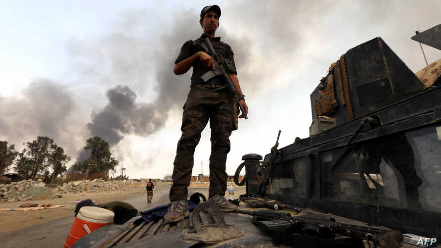 A member of the Iraqi government forces stands on a military vehicle as smoke billows from oil wells, set ablaze by Islamic State (IS) group militants before fleeing the oil-producing region of Qayyarah, Aug. 30, 2016.