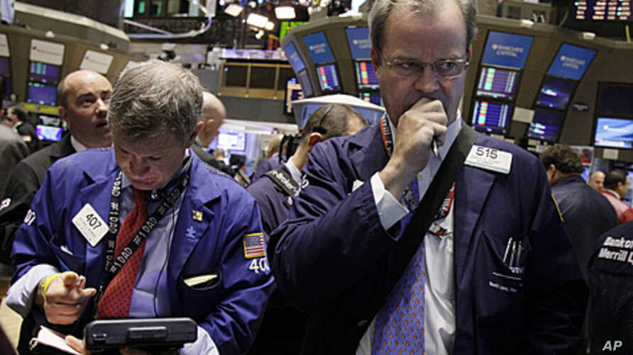 Traders Richard Newman, left, and David O'Day work on the floor of the New York Stock Exchange, June 14, 2011 (file photo)
