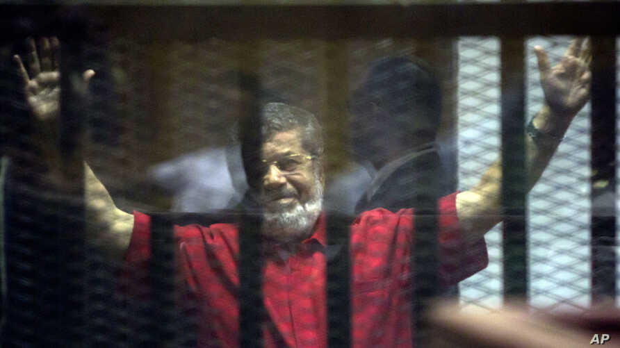 FILE - Former Egyptian President Mohammed Morsi, wearing a red jumpsuit that designates he has been sentenced to death, raises his hands inside a defendants cage in a makeshift courtroom at the national police academy, in an eastern suburb of Cairo.