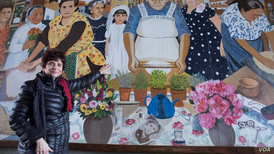 """Diane Modica points to her younger self, standing beside her late """"nonna,"""" an early 20th-century immigrant from Sicily. She and her grandmother were included in the City of Boston's """"Immigrant Grandmothers"""" mural in East Boston."""