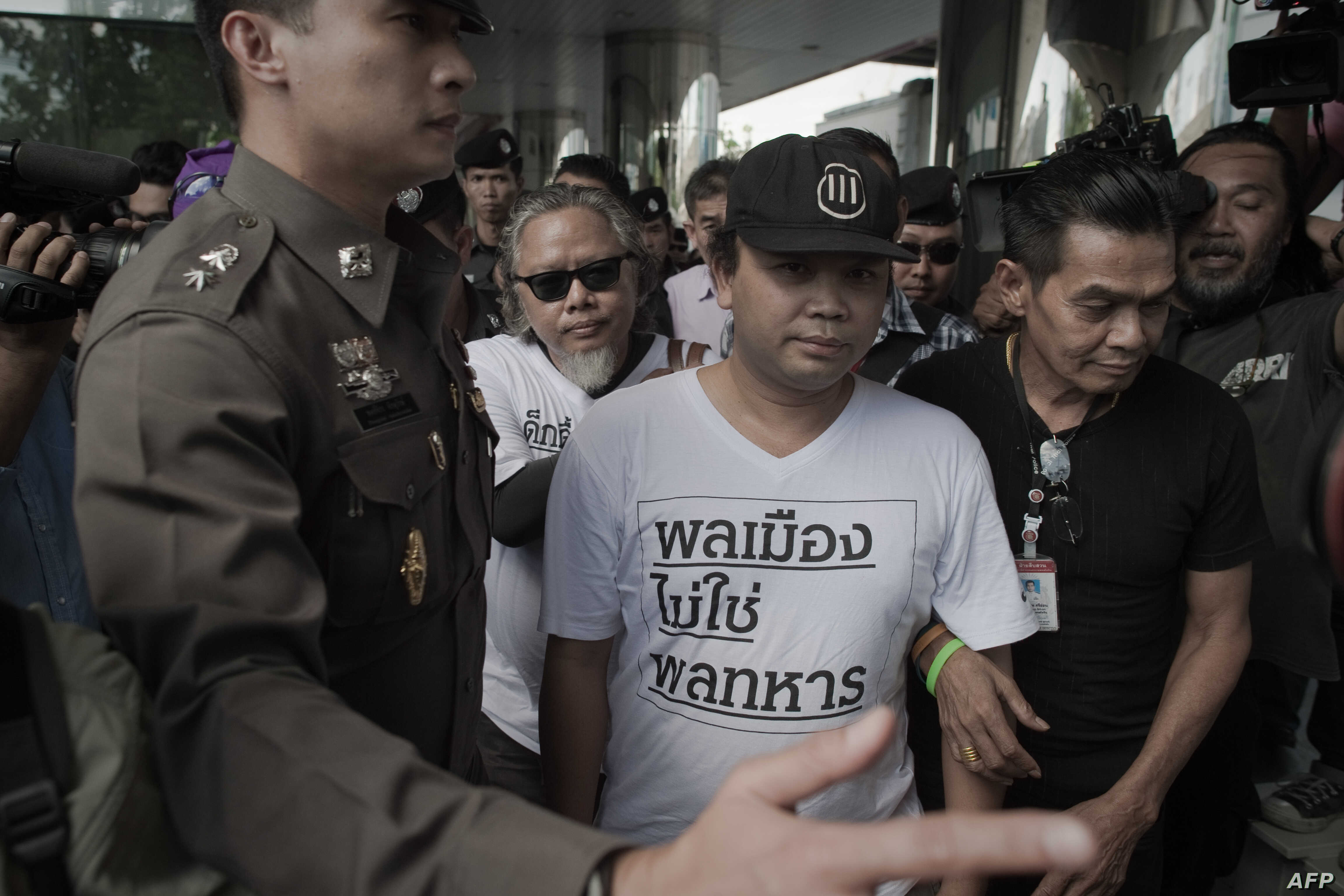 Two demonstrators (in white t-shirts) are arrested by police officers during a rally in Bangkok on May 22, 2015.