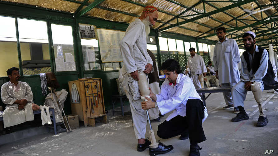FILE - A medic adjusts a prosthetic leg at the International Committee of the Red Cross orthopedic hospital in Kabul, Afghanistan, Saturday, July 17, 2010.
