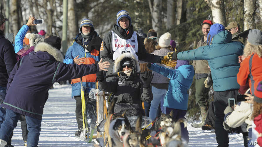 Defending Iditarod champion Joar Lefseth Ulsom of Norway greets fans on the trail during the ceremonial start of the Iditarod Trail Sled Dog Race, March 2, 2019, in Anchorage, Alaska.