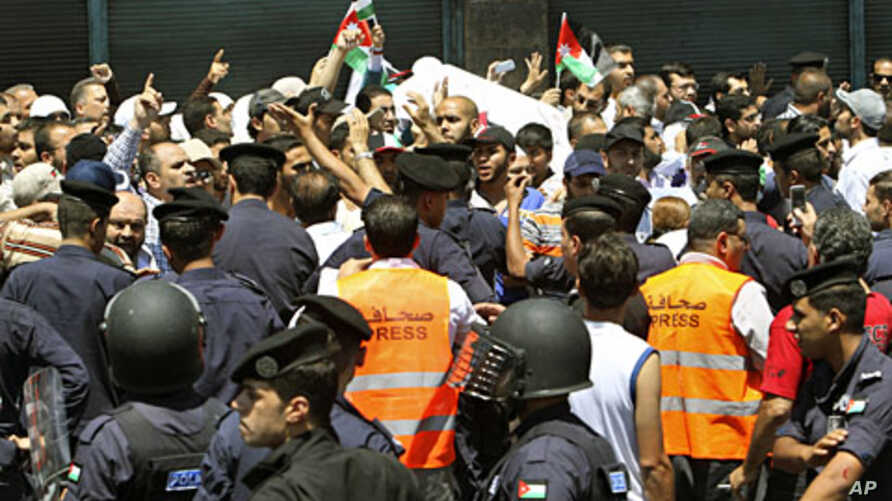 Police stand guard near protesters during a demonstration demanding the dissolution of the parliament and the departure of the government, after Friday prayers in Amman July 15, 2011