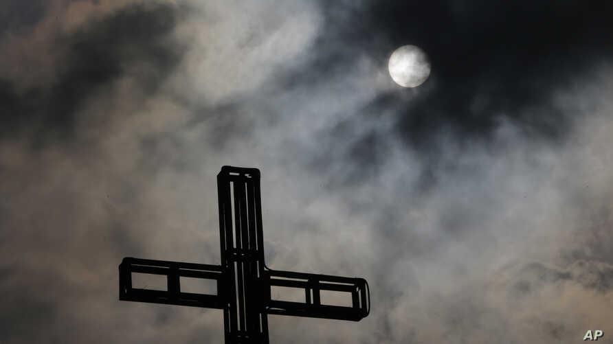 Dark clouds partially cover the sun in the sky above a church on Easter Sunday in suburban Quezon city, north of Manila, Philippines, April 5, 2015.