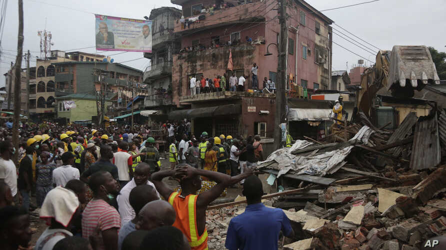 Rescue workers search for survivors amid the rubble of a collapsed building in a densely populated neighborhood in Lagos, Nigeria, July 25, 2017.