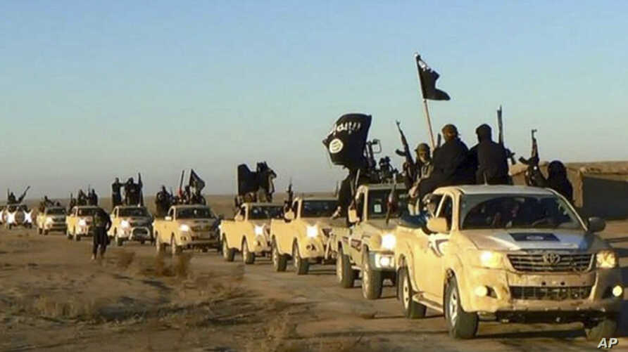 FILE - Militants of the Islamic State group hold up their weapons and wave flags on their vehicles in a convoy on a road leading to Iraq, while riding in Raqqa, Syria. The undated file photo was released by a militant website, which has been verifie
