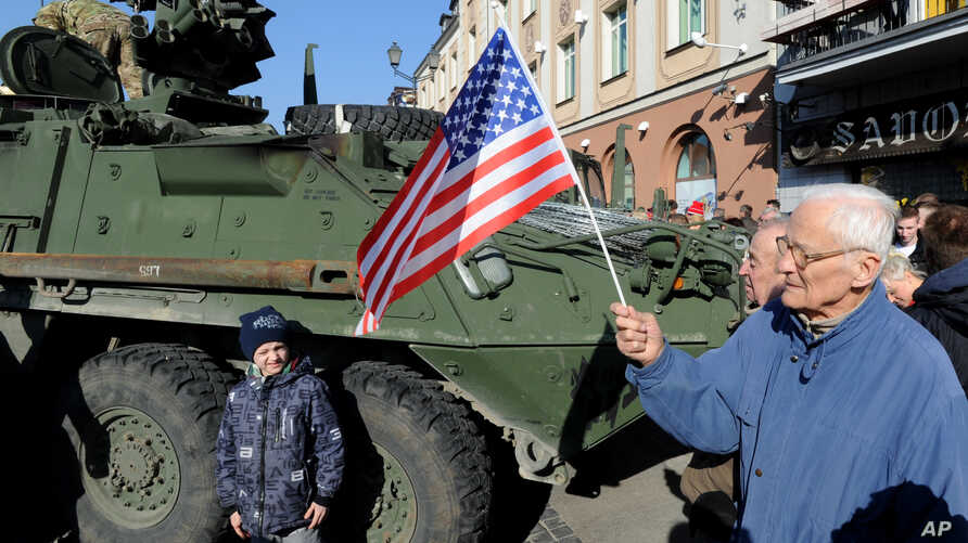 "FILE - A man holding a U.S. flag walks past a U.S. Army Stryker armored vehicle, part of ""Atlantic Resolve"" NATO exercises, passing through Bialystok, Poland, March 24, 2015."