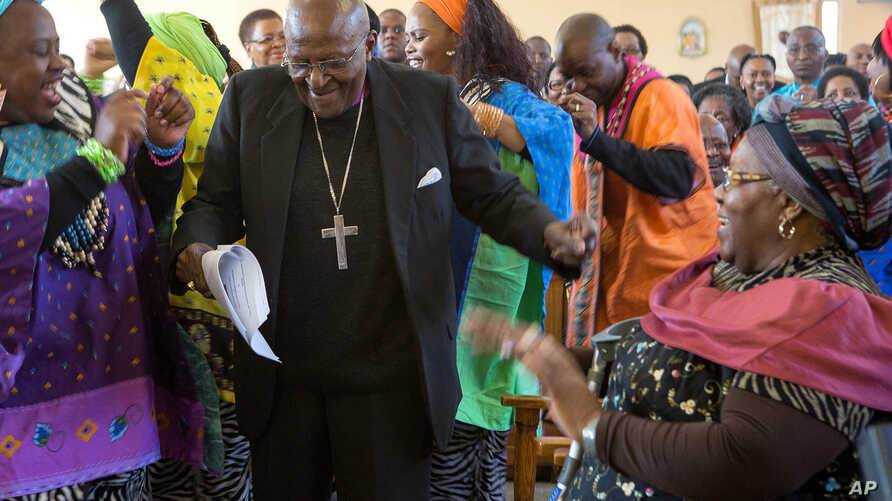 FILE - In this Saturday, July 4, 2015 file photo  retired Anglican Archbishop Desmond Tutu, centre, breaks into dance after renewing his wedding vows to his wife of 60 years, Leah, right, during a service in Soweto, Johannesburg.