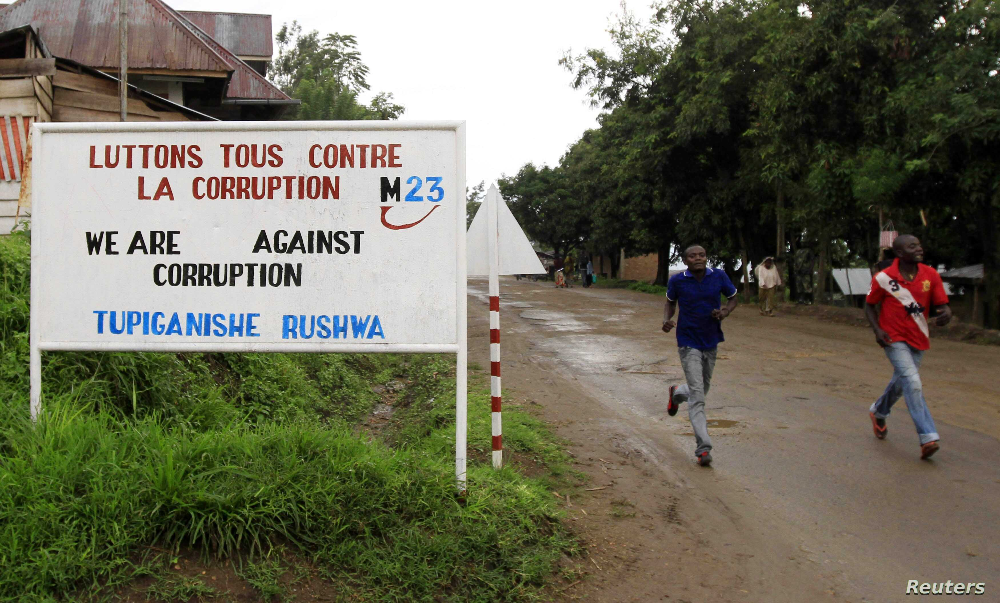 People jog past a sign, with a message by the M23 movement in their campaign against rampant corruption in the Democratic Republic of Congo, in an area under controlled of the Congolese Revolutionary Army (CRA) in Rutshuru town, November 3, 2012.