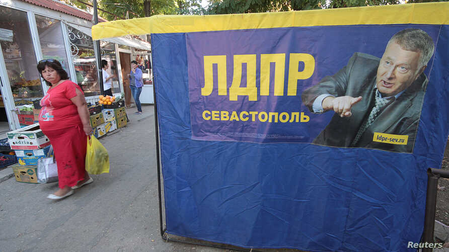 A woman walks past an election campaign poster of Vladimir Zhirinovsky, leader of Russian Liberal Democratic party, ahead of Sept. 18 parliamentary elections in the Black Sea port of Sevastopol, Crimea, Sept. 16, 2016.
