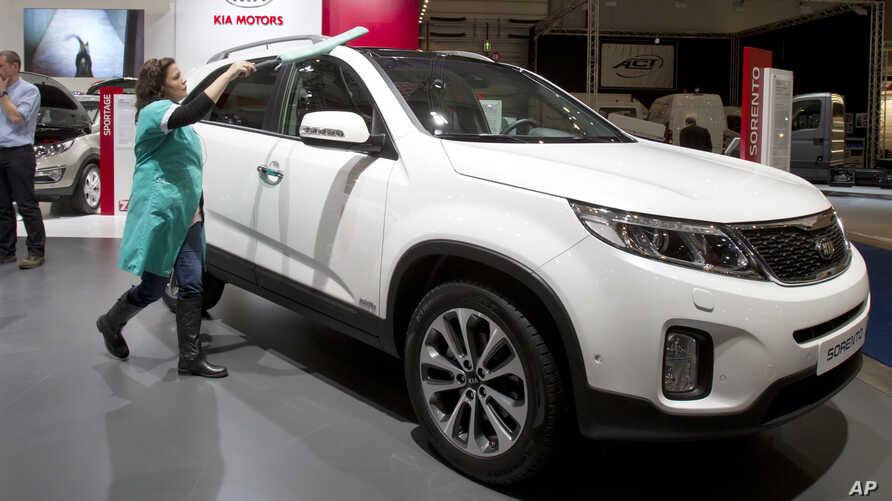 FILE - In this Jan. 10, 2013 photo, a worker polishes the new Kia Sorrento during the Brussels Motor Show at the Expo Center in Brussels.