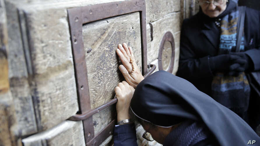 A woman prays outside the closed doors of the Church of the Holy Sepulcher, traditionally believed by many Christians to be the site of the crucifixion and burial of Jesus Christ, in Jerusalem, Feb. 27, 2018.