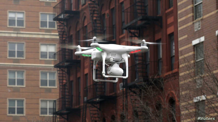 FILE - A drone flies near the scene where two buildings were destroyed in an explosion, in the East Harlem section in New York City, March 12, 2014.