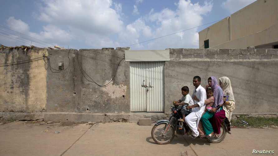 A family rides past the locked house of Rimsha Masih, a Pakistani Christian girl accused of blasphemy, on the outskirts of Islamabad, August 23, 2012.