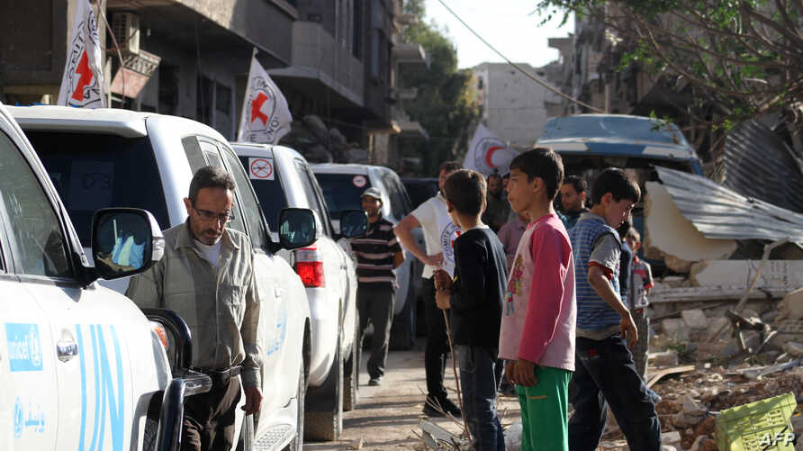Vehicles of the International Committee of the Red Cross (ICRC), the Syrian Arab Red Crescent and the United Nations wait on a street after an aid convoy entered the rebel-held Syrian town of Daraya, southwest of the capital Damascus, on June 1, 2016