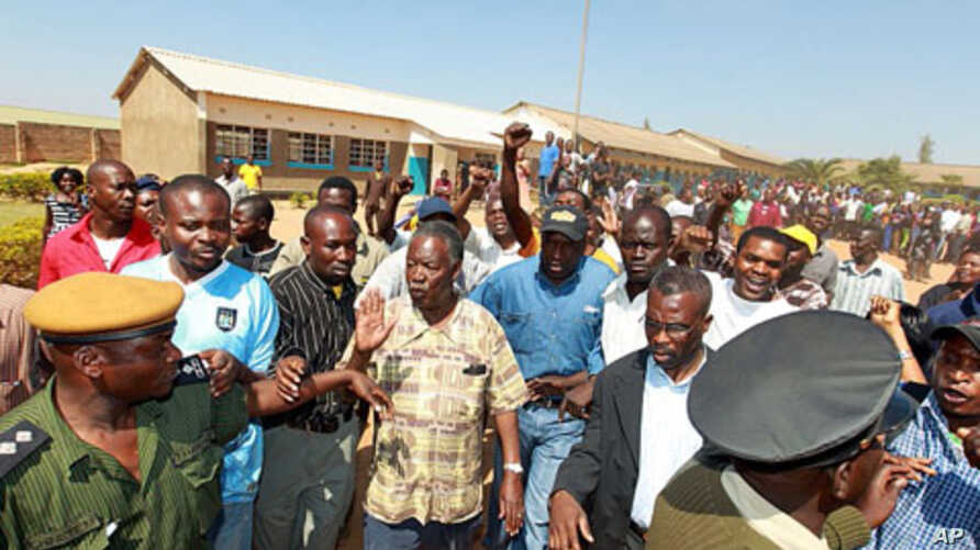 """The leader of the Zambian opposition Patriotic Front (PF), Michael """"King Cobra"""" Sata (C), leaves on September 20, 2011 a polling station after inspecting voting procedures in Lusaka during national elections."""