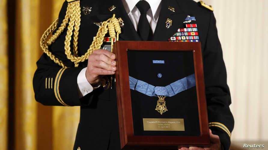 A U.S. Army officer holds a medal case displaying the Medal of Honor, the White House, April 11, 2013.