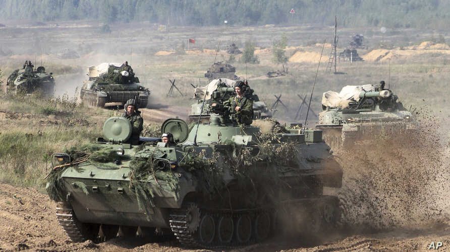 FILE - Belarusian army vehicles drive preparing for war games at an undisclosed location in Belarus, Sept. 11, 2017. Russia and Belarus are holding a massive war games, Zapad 2017, that due to start Thursday.