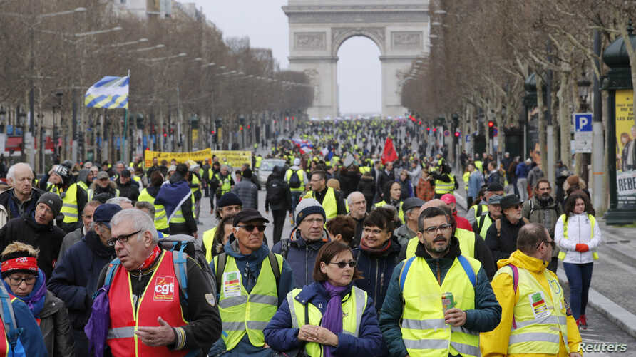 """Protesters walk down the Champs-Elysees during a demonstration by the """"yellow vest"""" movement in Paris, March 9, 2019."""