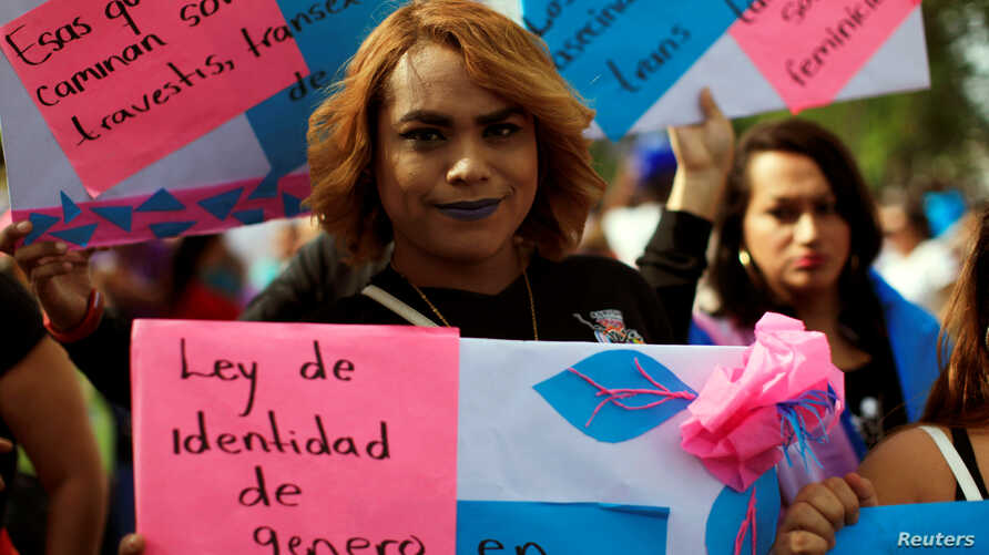 """A transgender woman participates in a demonstration to commemorate U.N. International Day for the Elimination of Violence against Women in San Salvador, El Salvador, Nov. 25, 2016. The front sign reads: """"Gender identity law now."""""""