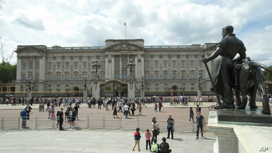 FILE - Tourists view the front facade of Buckingham Palace, the official London residence of Britain's Queen Elizabeth II, June 24, 2016.