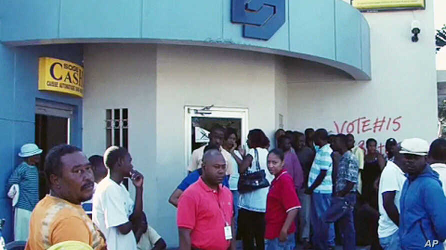 Customers line up outside a Port-au-Prince bank to withdraw money, 24 Jan 2010