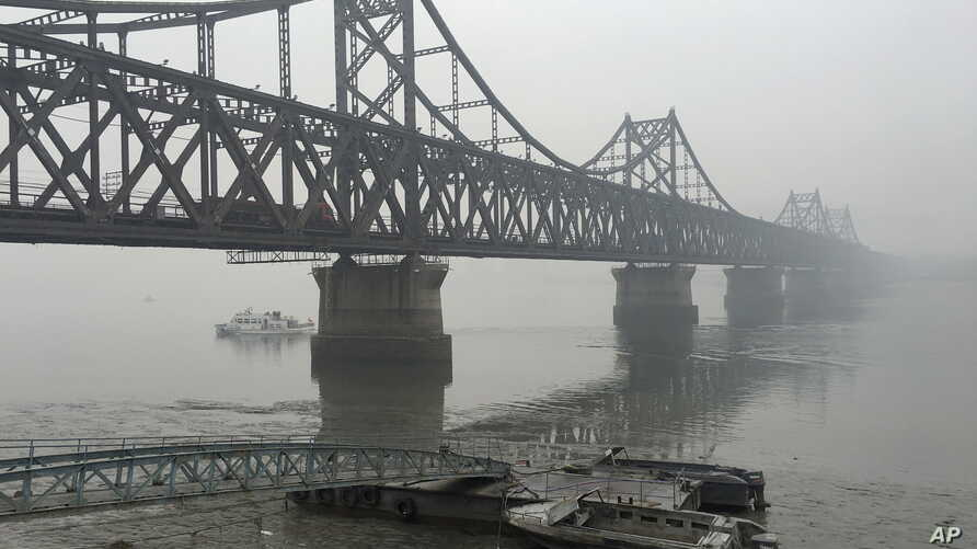 FILE - Trucks move across the bridge linking North Korea with the Chinese border city of Dandong in this March 3, 2016 photo.