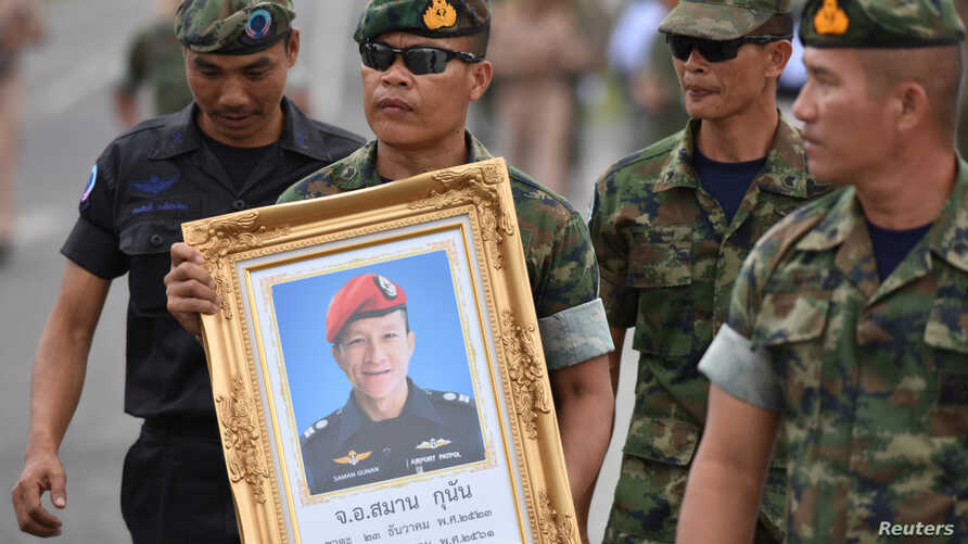An honor guard hold up a picture of Samarn Poonan, 38, a former member of Thailand's elite navy SEAL unit who died working to save 12 boys and their soccer coach trapped inside a flooded cave as family members weep at a airport, in Rayong province, T