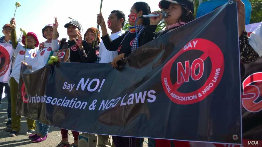 """Cambodian human rights and land activists holding banner that reads """"say NO! Union, Association & NGO Laws"""" during a protest in front of the National Assembly, in Phnom Penh, Cambodia, Sunday, June 28, 2015. (Hul Reaksmey/VOA Khmer)"""