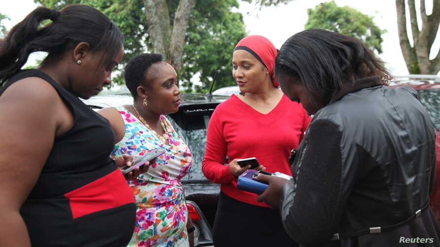Female taxi drivers Julie Wahome, Lydia Muchiri, Faridah Khamis and Agnes Mwongara chat at a parking lot in Nairobi, April 19, 2018.