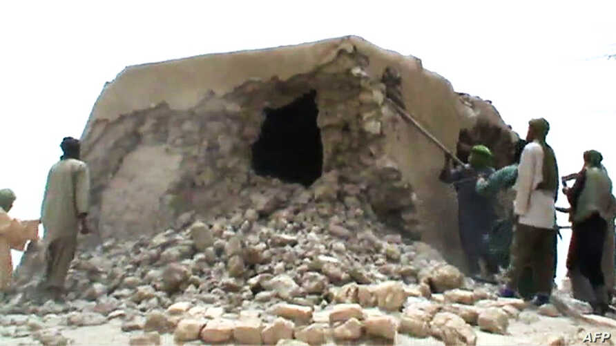 FILE - This file photo taken on July 1, 2012 shows a still from a video of Islamist militants destroying an ancient shrine in Timbuktu. The trial of a Malian jihadist charged with war crimes for ordering the 2012 destruction of 14 mausoleums of Musli...