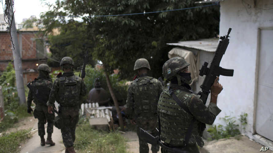 Soldiers on patrol walk through an alley at the Lins Complex of slums in Rio de Janeiro, Brazil, March 27, 2018. Thousands of troops and police are entering a complex of favelas in Rio de Janeiro in one of the largest operations since the military to