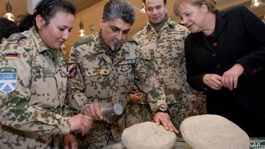 In a picture provided by the press department of German Government, German soldiers show off an 'Afghan fridge' made of  mud and straw to keep grapes fresh to  German Chancellor Angela Merkel  in Kunduz, Afghanistan, 18 Dec 2010